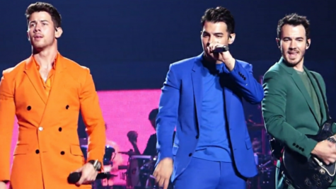 """Pictured above are the Jonas Brothers (left to right) Nick, Joe and Kevin performing on their 2019 """"Happiness Begins"""" tour."""