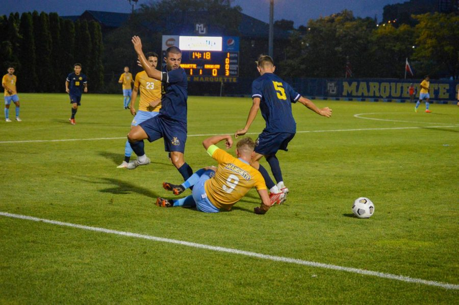 Lukas Sunesson (9) takes a slide tackle in Marquette's 2-1 win over Kansas City Sept. 3.
