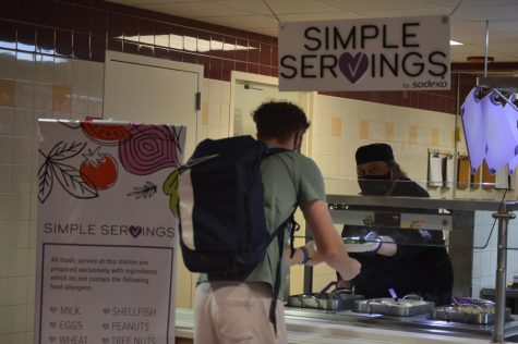 A student receiving food from the Simple Servings station